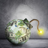 Bomb with ignited fuse. Bomb with dollars and euros and ignited fuse on grey wall background Stock Photography