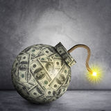 Bomb with ignited fuse. Bomb with dollars and ignited fuse on grey wall background Stock Photo
