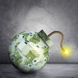 Bomb with ignited fuse. Bomb with euros and ignited fuse on grey wall background Royalty Free Stock Image