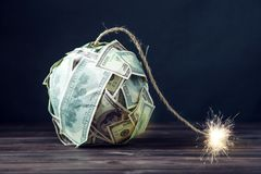 Bomb of money hundred dollar bills with a burning wick. Little time before the explosion. Concept of financial crisis. Big bomb of money hundred dollar bills Royalty Free Stock Photo