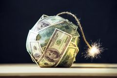 Bomb of money hundred dollar bills with a burning wick. Little time before the explosion. Concept of financial crisis. Big bomb of money hundred dollar bills Royalty Free Stock Images