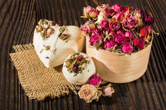 Bomb salt bath decorated with dried roses on a wooden background Stock Images