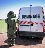 Bomb Squad (Deminage). Young male soldier in bomb suit behind bomb squad vehicle used by military to difuse and disarm explosive bombs Royalty Free Stock Photo
