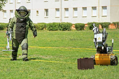 Bomb Squad. Young male soldier in bomb suit with a  bomb squad robot used by military to difuse and disarm explosive bombs Stock Photos