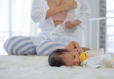 Bomba branca do leite materno do uso da mãe da camisa para obter o leite materno e o assento perto do sono recém-nascido na cama  fotografia de stock