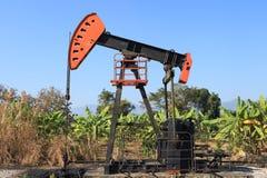 Bomba de óleo Jack (otário Rod Beam) no campo da banana Fotos de Stock Royalty Free