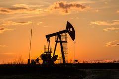 Bomba de aceite en puesta del sol Imágenes de archivo libres de regalías