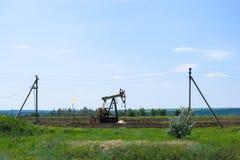 Bomba de aceite de trabajo en la tierra entre los campos verdes foto de archivo