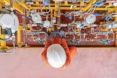 Bomba de diafragma de funcionamento do trabalhador a pouca distância do mar do serviço do petróleo e gás ajustando o curso da bom fotografia de stock royalty free