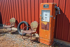 Bomba de gas retra y sillas aherrumbradas Imagen de archivo