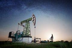 Bomba de óleo no campo petrolífero na noite Foto de Stock