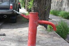 Bomba de mão velha da água no centro da cidade moderna Imagens de Stock Royalty Free