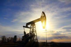 Bomba de petróleo de trabalho no por do sol Fotos de Stock Royalty Free