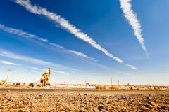 Bomba de petróleo en el desierto con el cielo asoleado Imagenes de archivo