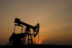 Bomba de petróleo en la puesta del sol Fotografía de archivo