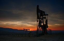 Bomba de petróleo en puesta del sol fotos de archivo