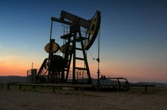 Bomba de petróleo en puesta del sol fotos de archivo libres de regalías