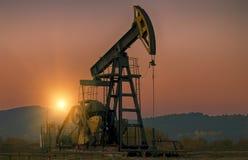 Bomba de petróleo en puesta del sol imagenes de archivo