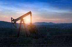 Bomba de petróleo en puesta del sol foto de archivo
