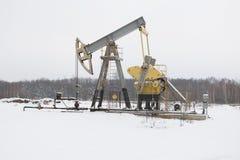 A bomba de petróleo funciona no fundo da floresta do inverno Fotografia de Stock Royalty Free
