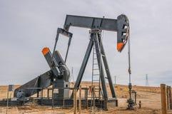 Bomba de poço de petróleo no campo petrolífero aberto desencapado Foto de Stock Royalty Free