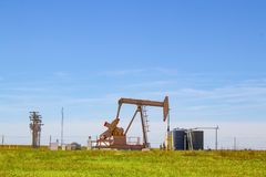 Bomba de trabalho Jack no poço de petróleo com os tanques no local para fora no horizonte nas planícies com linhas elétricas e no Foto de Stock Royalty Free