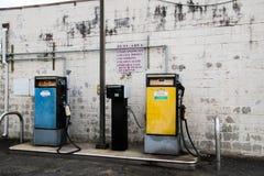 Bomba diesel amarela velha e bomba de gasolina azul velha na frente da parede de tijolo branca velha imagem de stock