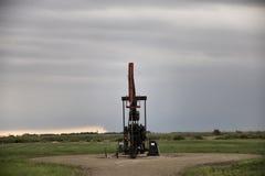 Bomba Jack del campo petrolífero de la tormenta Imagenes de archivo