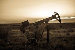 Bomba Jack del campo petrolífero en la puesta del sol Imagen de archivo