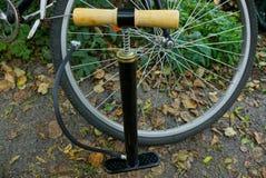 Bomba preta com a mangueira na roda de uma bicicleta na rua fotos de stock royalty free