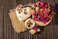 Bombardeie o banho de sal decorado com rosas secadas em um fundo de madeira Fotos de Stock Royalty Free