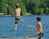 Bombardeio de mergulho do menino fora da doca no lago imagem de stock royalty free