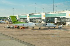 Bombardier Q400 of airBaltic is being loaded at Arlanda International Airport. STOCKHOLM, SWEDEN - JULY 12, 2018 : Bombardier Q400 of airBaltic is being loaded royalty free stock image