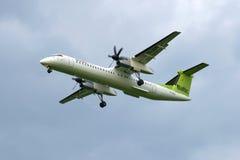 Bombardiera junakowania 8-Q402 linie lotnicze Wietrzą Bałtyckiego na tle chmurny niebo (YL-BAI) Zdjęcie Stock