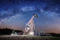 Bombas de óleo no campo petrolífero na noite Imagens de Stock