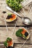 Bombas del bocado con el caviar rojo y negro imagen de archivo