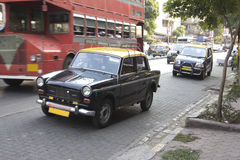 Bombay Taxi. Taxis in Bombay. In the background is a typical Bombay bus Stock Image