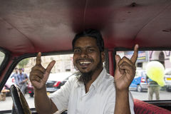 Bombay Taxy Driver. A Bombay Taxi driver is sitting in his Taxi laughing merrily Stock Image
