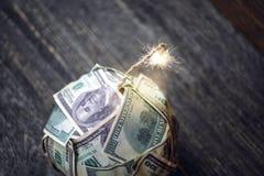 Bombe des Geldes, Hundertdollar-Rechnungen mit einer brennenden Sicherung Explosion von Anlagem?rkten Das Diagramm des Fallens ei stockfotografie