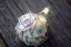 Bombe des Geldes, Hundertdollar-Rechnungen mit einer brennenden Sicherung Explosion von Anlagem?rkten Das Diagramm des Fallens ei stockbild
