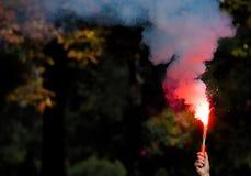 Bombe fumigène rouge dans une main photo libre de droits