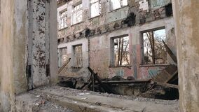 A bombed-out abandoned building with a broken roof and walls
