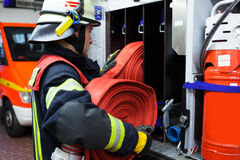 Bombeiro com mangueira da água em um firetruck Fotos de Stock Royalty Free