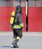 Bombeiro com o tanque de oxigênio a respirar durante o fogo foto de stock