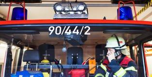 Bombeiro em um carro de bombeiros e faísca com grupo de rádios imagem de stock
