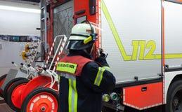 Bombeiro em uma faísca do carro de bombeiros do departamento dos bombeiros com grupo de rádios imagens de stock royalty free