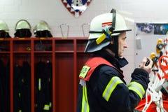 Bombeiro em uma faísca do departamento dos bombeiros com grupo de rádios imagens de stock