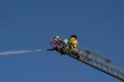Bombeiro na água do pulverizador do caminhão de escada no incêndio Fotos de Stock