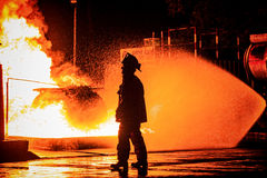 Bombeiro que anda na frente do fogo Fotos de Stock Royalty Free