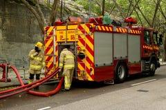 Bombeiros e carro de bombeiros Fotografia de Stock Royalty Free